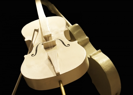 cellos: Two elegant golden cellos  instrument isolated on black background
