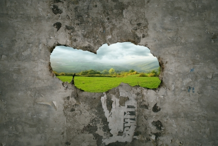 Beautiful fantasy imagine representing a hole crack in a old wall with a view of a landscape through it Фото со стока
