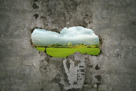 Mooie fantasie stel die een gat scheur in een oude muur met een weergave van een landschap doorheen