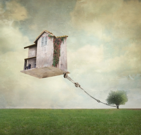 Artistic image representing an house floating in the air tied to a rope to the tree in a surreal vintage background