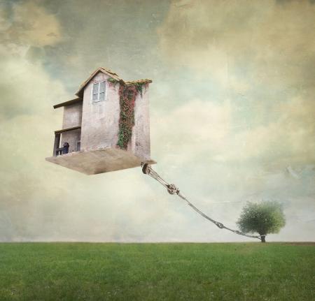 Artistieke afbeelding van een huis in de lucht zweven vastgebonden aan een touw om de boom in een surrealistische vintage achtergrond