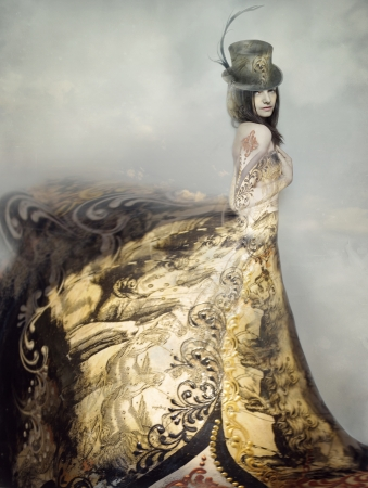 Beautiful artistic portrait of an extravagant lady in an eighteen century style dress and cylinder with clouds in the background