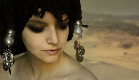mysterious woman: Beautiful artistic portrait of a young woman with black turban and accessories in the desert