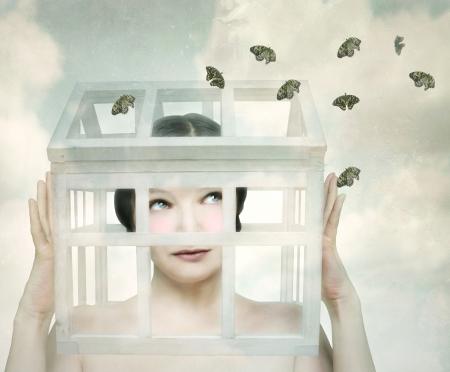 Surreal meisje met een kleine houten en glazen en klein huis in haar hoofd dat de vlinders kijkt naar buiten Stockfoto