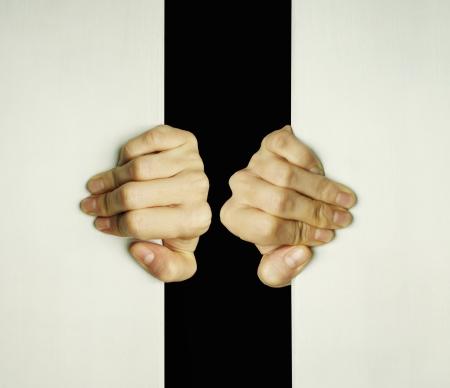 slit: Concepto de dos manos tratando de abrir una rendija para salir de la oscuridad