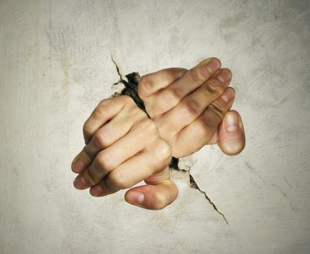 Concept van twee handen probeert moeilijk om eruit te komen van het breken van de muur