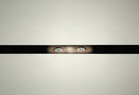 Conceptual eyes watching throw a slit with curiosity in the darkness