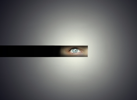 One human eye watching throw a slit with curiosity in the darkness