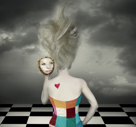 Sensual and fantasy back of a female model with long blond hair and corset who looks at her face in a mirror in a surreal background