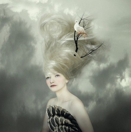Sophisticated and artistic portrait of a beautiful female model with a white dove on a branch in the very long blond hair  photo