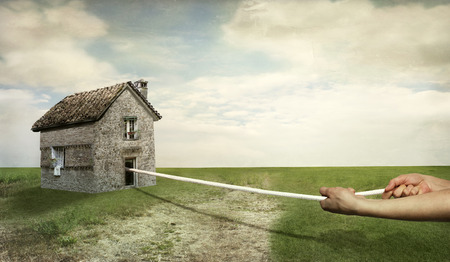 imaginative: A beautiful landscape with two human hands that pull an house with a rope Stock Photo