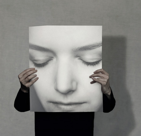 shadow face: Person who holds a large female portrait on grey background