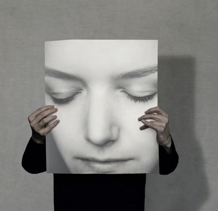 Persoon die een grote vrouwelijke portret op grijze achtergrond houdt Stockfoto