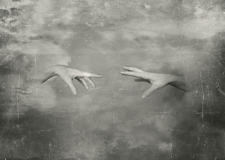 Two hands that trying to touch in black and white  photo