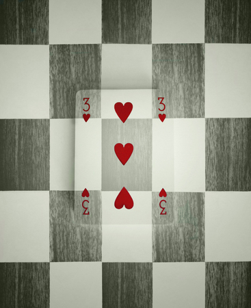 Three hearts of a common playing card camouflaged with the checkered background photo