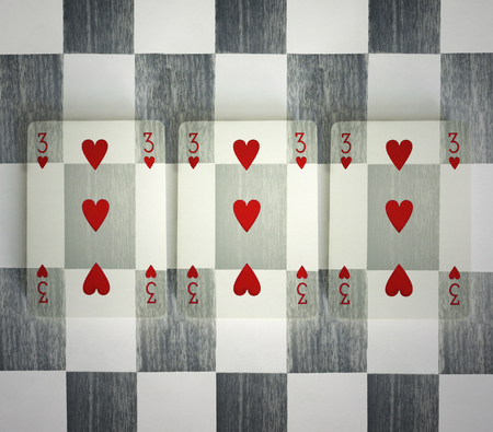 Three hearts of a common playing cards camouflaged with the checkered background photo