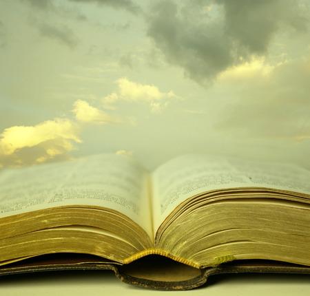 bible ouverte: D�tail d'une vieille bible sainte ouverte avec une belle et mystique ciel en arri�re-plan dans une lumi�re dor�e