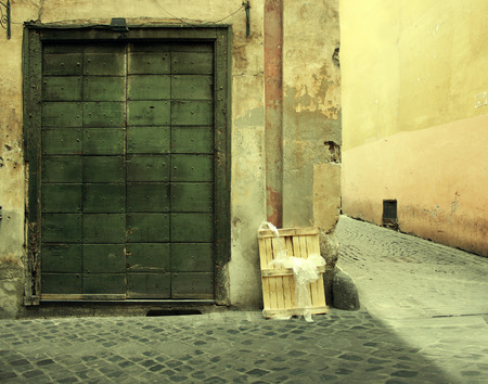 unique characteristics: An antique and neglected facade with a big door and a side alley in Rome