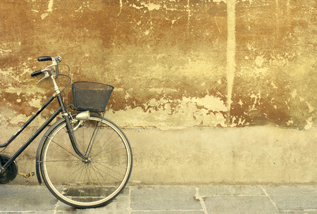detail of a part of a bicycle leaning against an old wall photo