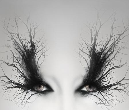 Twee artistieke vrouwelijke ogen met decoratie van takken om hen heen als een make-up in een lichtgrijze achtergrond