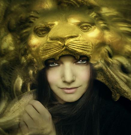 雄大なゴールデン ライオンの顔のマスクを持つ美しい若い女性の功妙な肖像画 写真素材