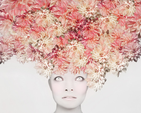 Beautiful artistic portrait of a young woman with an extravagant colorful floral headdress
