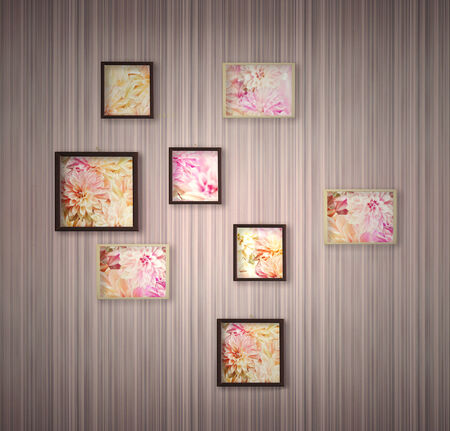hung: Pink stripped wallpaper with hung a variety of picture frames with colorful detail of flowers inside   Stock Photo
