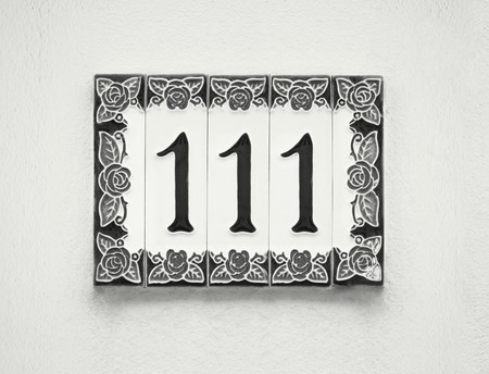 Detail of the number one hundred and eleven in black and white