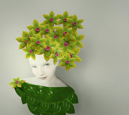 surrealist: Surreal artistic portrait of a young woman with a bizarre headdress and costume made of leaves and flower fabric Stock Photo