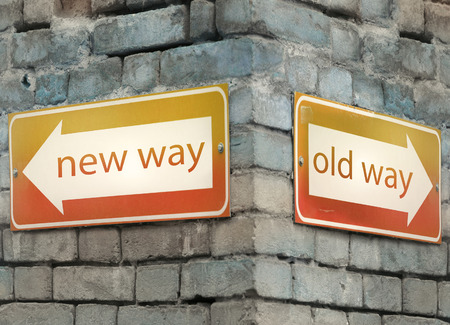 new direction: Two direction arrow at the angle of an old brick wall with the text new and old way