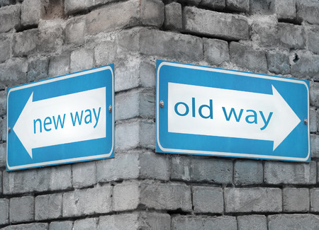 new direction: Two blue light directions arrow at the angle on a grey old brick wall with the text new and old way