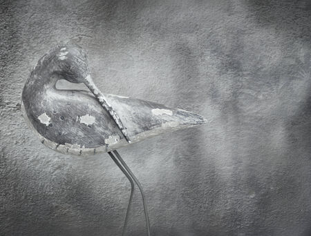 lightness: Beautiful elegant image of a stylized sculpture bird with a consumed and dark wall in the background