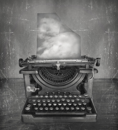 surrealism: Surreal imagine in black and white of a beautiful classic old fashioned typewriter with a paper with clouds in a vintage style