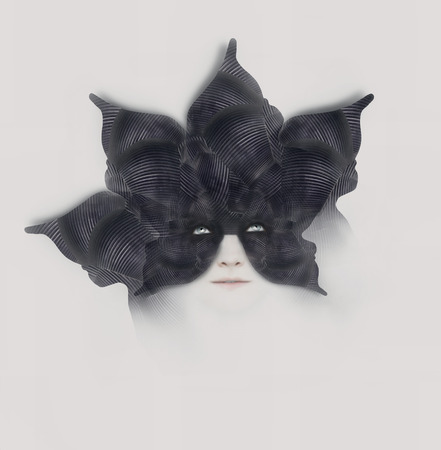 Beautiful surreal artistic portrait of a female with a bizarre black mask-hat shaped with like a flower with petals on white background