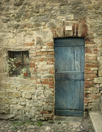 barn door: Detail of an old facade with door and a little window of a farmhouse Stock Photo