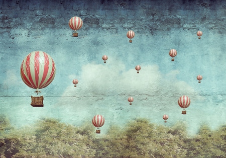 Many hot air balloons flying over a forest Stock Photo