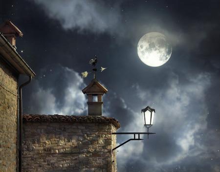 Antieke daken met windwijzer haan en schoorstenen in een mooie nacht hemel met volle maan en wolken Stockfoto