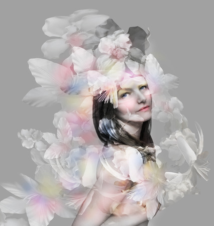 Beautiful extravagant and artistic portrait of a beautiful girl with floral decorations on a gray background Stock Photo