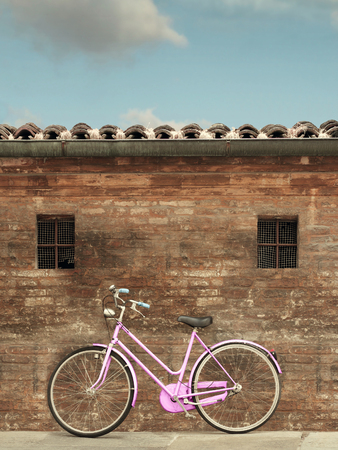 roof windows: Bicycle parked and leaning on an old brick wall with two small windows, the roof and the sky