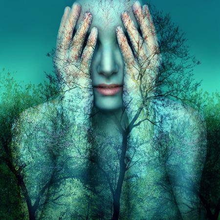 나무와 하늘의 배경에 그녀의 손으로 그녀의 눈을 커버하는 여자의 초현실적 인 예술 이미지