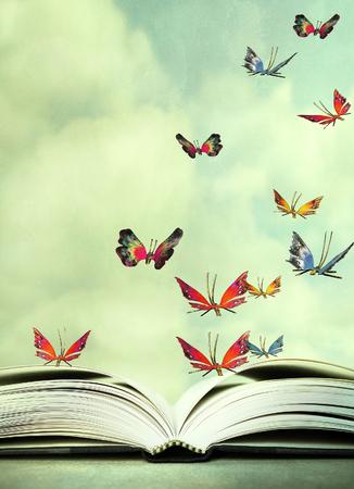 Imagen artística de un libro abierto y coloridas mariposas que revolotean en el cielo Foto de archivo