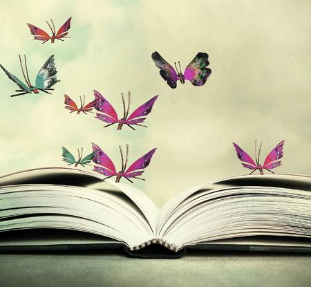 하늘에서 마우스를 펼친 책과 화려한 나비의 예술적 이미지