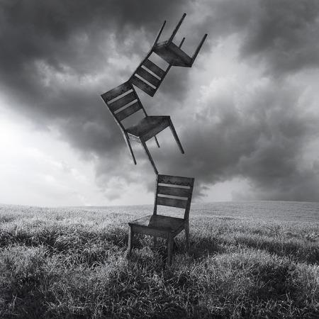 Een surrealistisch conceptueel beeld dat drie vliegende bewegende stoelen vertegenwoordigt die in een weide met een dramatische en bewolkte hemel in zwart-wit worden geïsoleerd