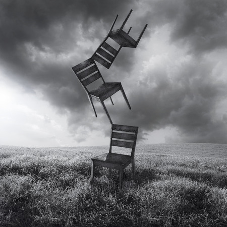 A surreal conceptual image representing three flying moving chairs isolated in a meadow with a dramatic and cloudy sky in black and white