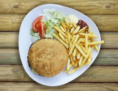 Photo from top of a plate with Cheeseburger chips and sauces on a wooden table