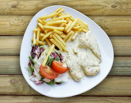 Photo from top of a plate with Aromatic Chicken with chips and mixed salad on a wooden table