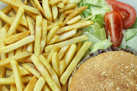 A close up from top of French Fries Cheeseburger salade and tomatoes