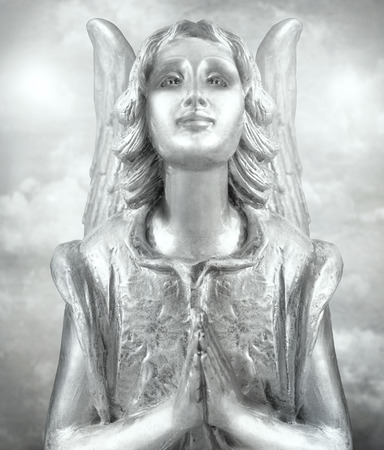 A beautiful silvery angel praying with cloudy sky on his back in black and white