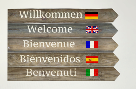 Wooden signboard showing welcome in five different languages with their flags and indications on light grey background 免版税图像
