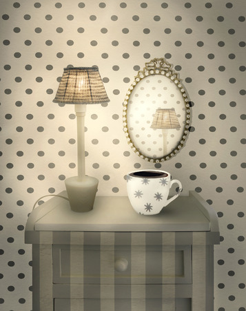 Beautiful interior detail of a bedside table with lighted lamp a cup and an oval mirror in a cozy environment